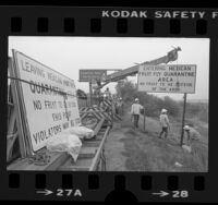 "Caltrans workers erecting sign reading ""Entering Mexican Fruit Fly Quarantine Area"" along Long Beach Freeway, South Gate (Calif.), 1983"