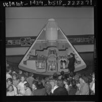 Three students sitting in Apollo spacecraft mockup as William F. Fitzgerald and students watch at Exposition Park in Los Angeles, 1963