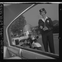 South Pasadena's first female police officer, Shirley Largent, issuing parking ticket, Calif., 1963