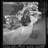 California's Junior Miss of 1963-64, Kim Carnes seated, sewing on gown she will wear in the Rose Parade