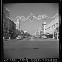 Street scene of 3rd Street with holiday ornaments strung across street in Santa Monica, Calif., 1963