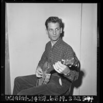 Folk musician Mike Seeger seated in chair playing banjo, Calif., 1964