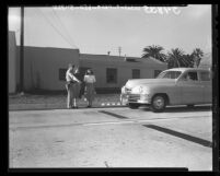 Lt. R. W. Cooley shows new treadles on highway which, when tripped by car operates signal in Santa Monica, Calif., 1948