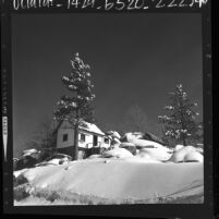 Cottage surrounded by snow covered boulders and trees near Arrowbear, Calif., 1964