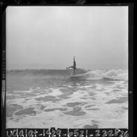 Lone male surfer riding a wave at Leo Carrillo Beach, Malibu, 1964