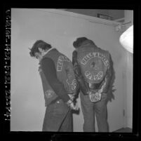 Two Hell's Angels motorcycle gang members in handcuffs, facing wall showing designs on back jackets in Los Angeles, Calif.