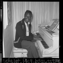 Singer Nat King Cole playing piano at his home in Los Angeles, Calif., 1964