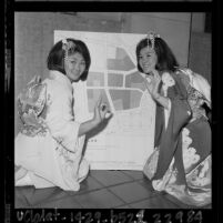 "Two Japanese American woman in kimonos giving  ""o.k."" hand sign to map showing redevelopment plan for Los Angeles' Little Tokyo, 1964"