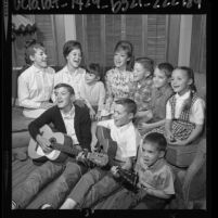 Singing group, the Singing Lennon Sisters, sitting on couch with seven younger siblings in Venice, Calif., 1964