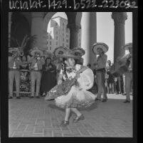 Mexican American girl in costume dancing with mariachi band at opening of Good Neighbor Week in Los Angeles, Calif., 1964