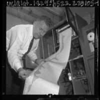 James Ledbetter examining results of air monitoring station in Burbank, Calif., 1964