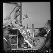 Myrlie Evers handing city worker Ted R. Aurand new Evers Ave. street sign in Compton, Calif., 1964