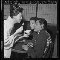 Kawafuku employee Chiyo Tota offering rice to boxers Fabian Esquivel and Hiroyuki Ebihara, 1964