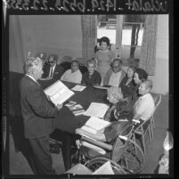 Man conducting an United States immigration class to a group of elderly immigrants at the International Institute of Los Angeles, Calif., 1964