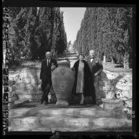 Harry E. Benedict, Mrs. Frank Vanderlip, Frank Vanderlip Jr. standing before cypress trees at Portuguese Bend, 1964
