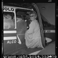 Joan A. Merriam Smith loading plane in preparation for solo around the world flight, Calif., 1964