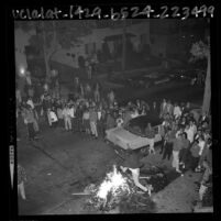 UCLA students gathering around bonfire set ablaze on residential street to celebrate UCLA's 1964 win over Duke in basketball