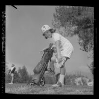 Seven year old Beverly Klass adjusting her shoe during competition in Los Angeles City Junior Golf Tournament, 1964