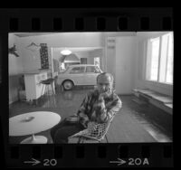 Emil Seliga sitting in the rumpus room of his Los Angeles, Calif. home along with the family's British MG automobile, 1964