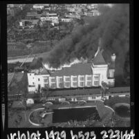 Aerial view of the Deauville Beach Club as flames and smoke from arson fire burn thru roof in Santa Monica, Calif., 1964