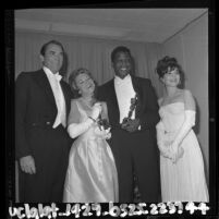 Sidney Poitier holding his Oscar pose with Gregory Peck, Annabella and Anne Bancroft backstage at the Academy Awards, Los Angeles, 1964