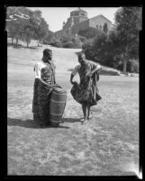 Ghanaians Robert Bonsu and Jerry Sowah rehearsing tribal dance on slope below Powell Library on UCLA campus, 1964