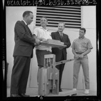 Peace Corps directors Dr. Robert H. Ewald and Dr. Robert Callahan with two trainees using brick making machine in Los Angeles, Calif., 1964