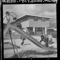 Four boys playing on slide in playground at San Fernando Gardens Housing Project, Calif., 1964