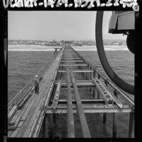 Construction Venice Beach pier; view from ocean looking towards the beach, Calif., 1964