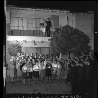 USC Delta Tau Deltas at UCLA Kappa Kappa Gamma sorority house serenade one another to celebrate couples pinning, 1964