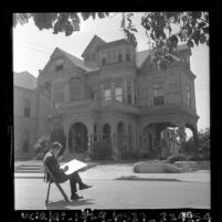 Artist Leo Politi sketching in front of The Castle, a Victorian house at 325 Bunker Hill Ave. in Los Angeles, 1964