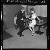 Man in suit and woman in fringed mini skirt, dancing the Go-Go at Sunset Strip nightclub in Los Angeles, Calif., 1964
