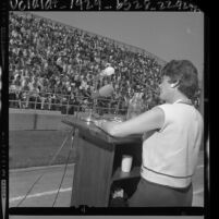 Dorothy Healey podium speaking to crowd in bleachers at Cal State Los Angeles, 1964