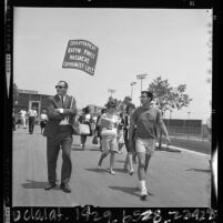 "Cal State Los Angeles students, one with ""Communist Lies"" placard walking to Dorothy Healey speech, 1964"