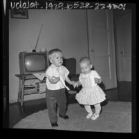 Two year old Billy Webb who was born with birth defect caused by Thalidomide, at his home dancing with younger sister in Gardena, Calif., 1964