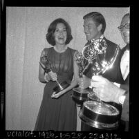 Mary Tyler Moore, Dick Van Dyke, and Sheldon Leonard holding their awards backstage at Emmy Awards, 1964
