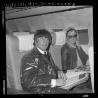 John Lennon and wife Cynthia sitting in airplane on stop over in Los Angeles, Calif., 1964