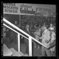 Barry Goldwater surrounded by supporters and banners as he walks towards stage to deliver speech at Knott's Berry Farm, 1964
