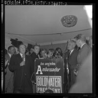 Barry Goldwater standing at podium surrounded by press and supporters during election returns in 1964 California primary
