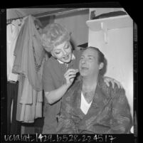 """Nancy Andrews applying makeup to Sid Caesar backstage before """"Little Me"""" show at Philharmonic Auditorium, Los Angeles, Calif., 1964"""