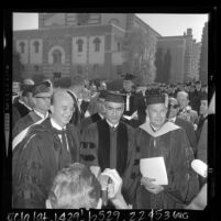 Shah of Iran, Mohammed Reza Pahlavi flanked by Dr. Clark Kerr and Franklin D. Murphy on UCLA campus after receiving honorary degree, Los Angeles, 1964