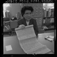 Mrs. Man Hing Mok, head of UCLA Oriental Library holding ancient Tibetan manuscript-scroll, 1964