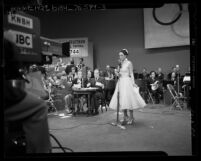 Dorothy Lamour standing at microphone as Bing Crosby and Bob Hope watch at telethon for 1952 Olympic Games