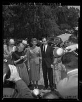 Rita Hayworth and estranged husband Aly Kahn surrounded by reporters outside Hayworth's home, 1952