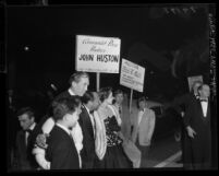 "Supporters of the Un-American Activities Committee picketing director John Huston as he arrives at ""Moulin Rouge"" premiere in Los Angeles, Calif., 1952"