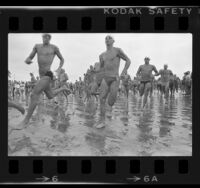 Athletes in swimsuits sprinting along beach at start of the Bud Light U.S. Triathlon Series in Long Beach, Calif., 1984