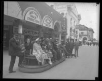 People riding boardwalk trolley as it passes auction house and Neptune Theatre in Venice, Calif., circa 1925
