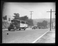 """Automobiles following bus with sign reading """"California Caravan New York to Santa Monica,"""" Calif., circa 1930"""