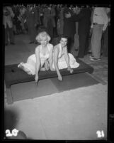 Marilyn Monroe and Jane Russell putting signatures in cement at Chinese Theater, Hollywood (Los Angeles), 1953