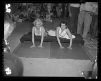 Marilyn Monroe and Jane Russell putting hand prints in cement at Chinese Theater, Hollywood (Los Angeles), 1953